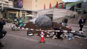 """Ein 3 x 2 Meter großes, rauchendes Objekt tauchte gestern mitten in Berlin-Charlottenburg auf. Dem Anschein nach hatte es ein riesiges Loch in den Gehweg vor dem denkmalgeschützten Bikini-Haus gerissen. Hinter der vermeintlichen Alien-Invasion steckte eine Aktion des Seriensenders Fox zum Start der Neuauflage von """"Krieg der Welten"""". (Foto: FOX)"""